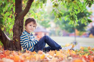 Little toddler boy, eating apple in the afternoon, sitting under apple tree, relaxing